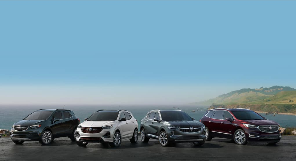 Four Buick-GMC vehicles, shown from the front, overlooking ocean cliffs