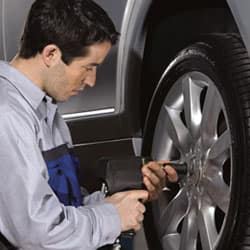 Mechanic working on a tire of a Mercedes Benz vehicle
