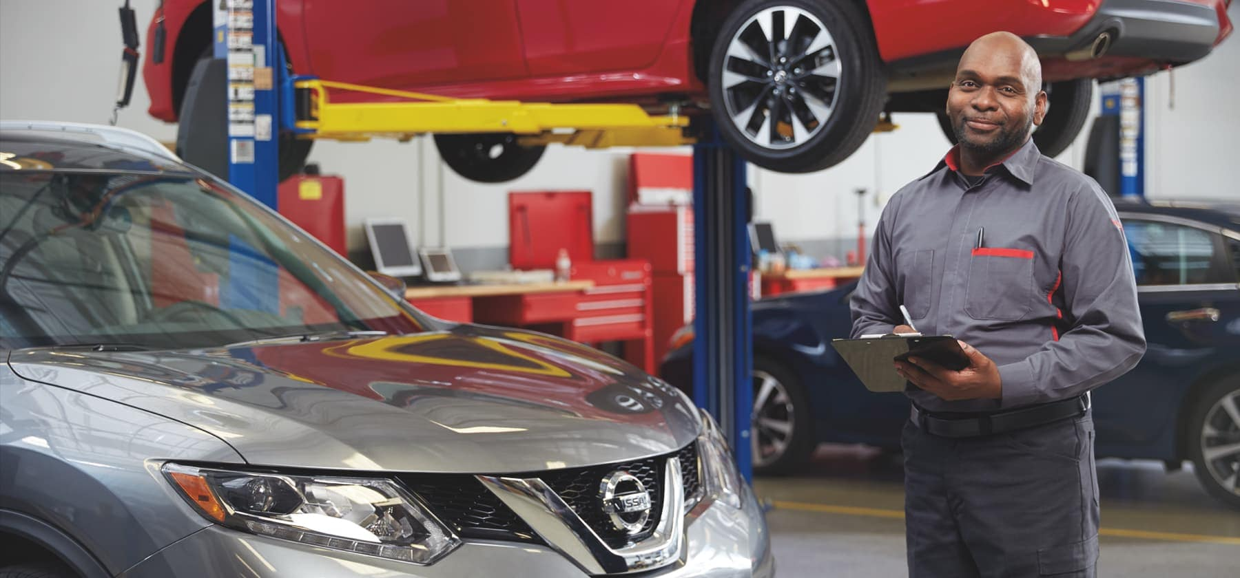 Mechanic standing by silver Nissan SUV